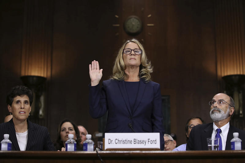 Christine Blasey Ford is sworn in before the Senate Judiciary Committee, Thursday, Sept. 27, 2018 in Washington. Her attorney's Debra Katz and Michael Bromwich watch.
