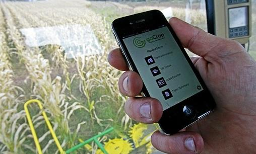 In this file photo, Tony Pouliot demonstrates the goCrop app on his mobile photo in the cab of his combine on his farm in Westford, Vt.