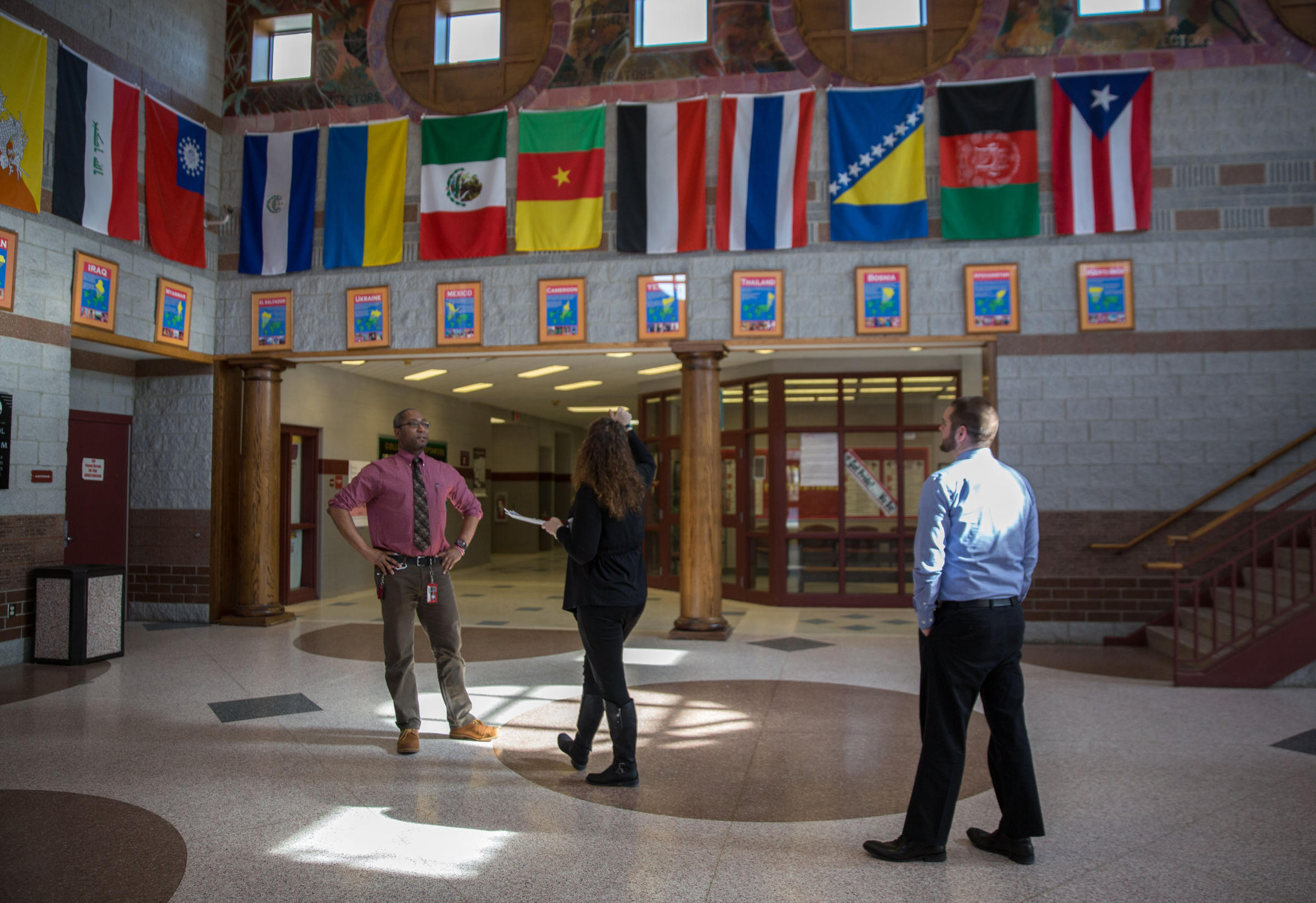 Teachers at East High School (from left to right): Milton Robinson, Heather  Kensill, and Mike Costa check out flags representing the countries of  origin for ...