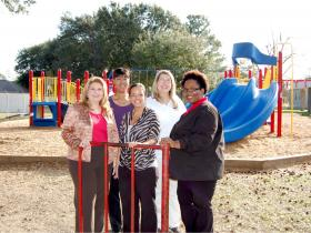 Twin Oaks Elementary teachers pose with the old rusty red gate with the new playground behind them.