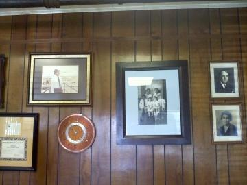 Old family photos of the Daigle family hang on the wall in the main office at the mill. (Tegan Wendland/WRKF)