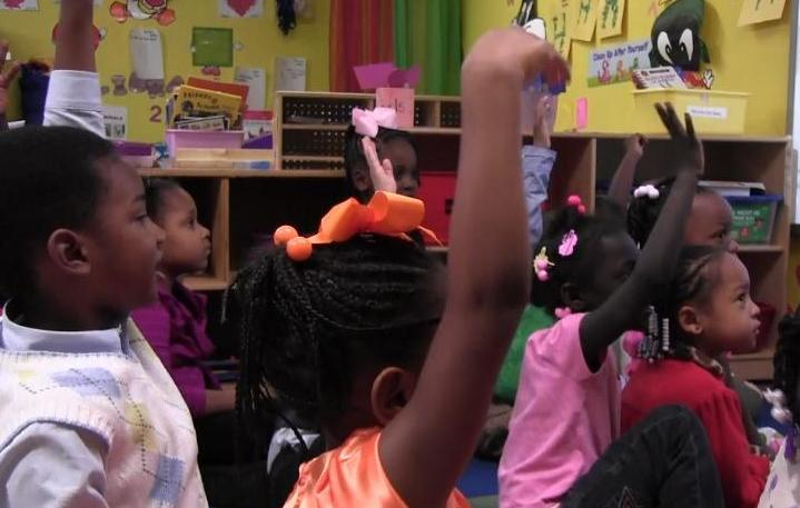 Pre-K students raise their hands to answer a question in an LA-4 class.