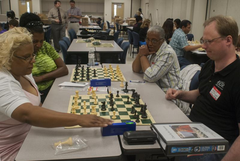 Clairborne Elementary gifted resource teacher Chris Wilson (front right) plays special education resource teacher Annie Fox in the chess tournament as Audubon Elementary computer lab teacher Contessa Hunt (back left) and Melsrose Elementary fourth grade t