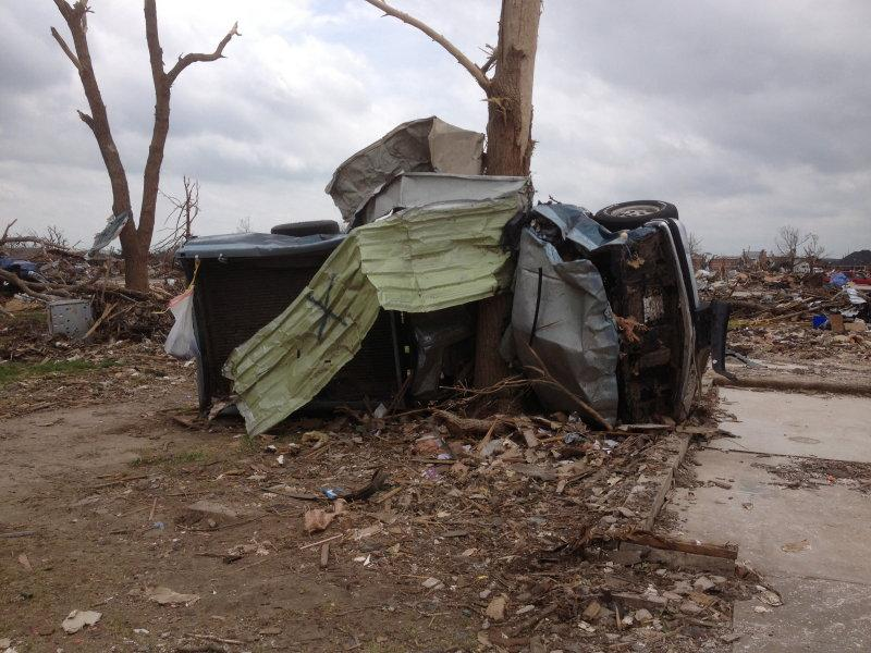 A pickup truck wrapped around a tree in the aftermath of a tornado in Oklahoma.