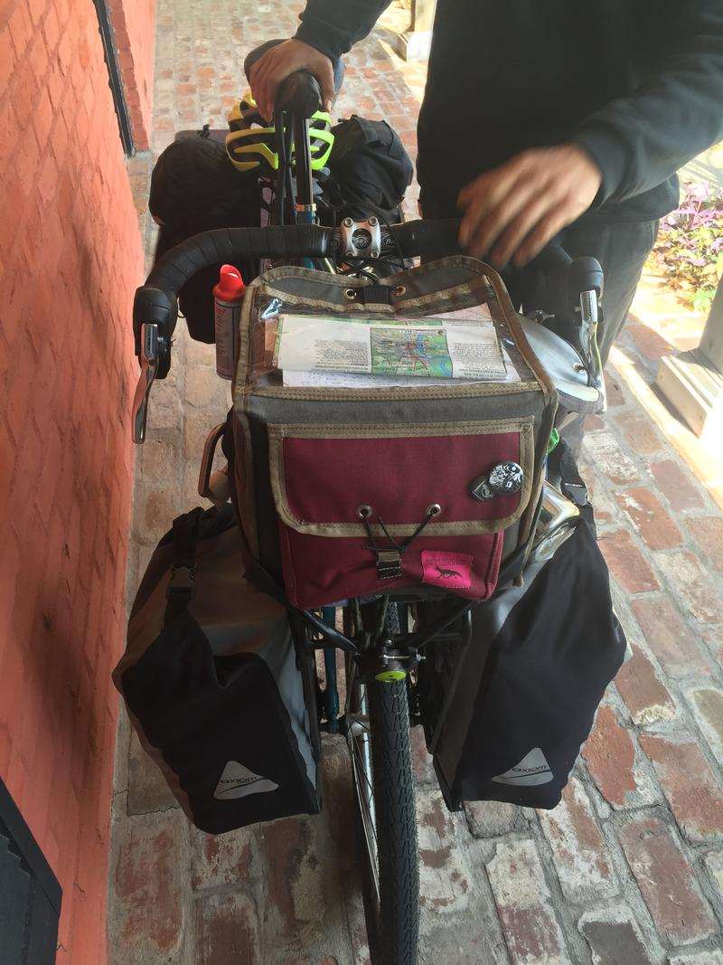 A map inside a protective cover sits atop Joey's handlebar bag. Inside are books, snacks, chargers, and more maps.