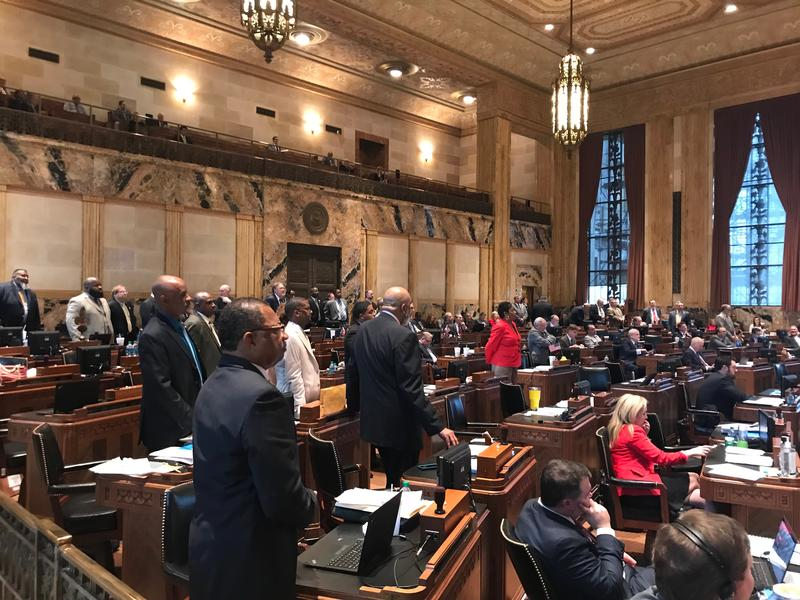 Members of the Legislative Black Caucus stand as Rep. Ted James (D-Baton Rouge), a member of the caucus, explains the group's concern with budget negotiations on the House floor.