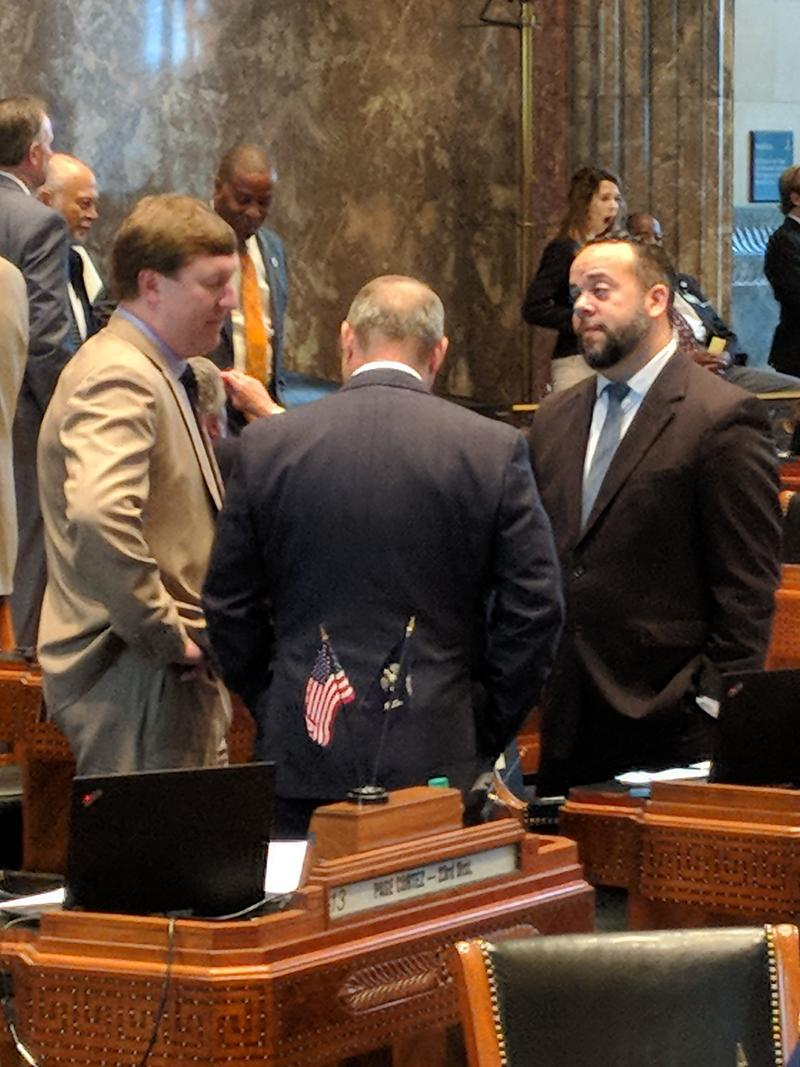 Sen. J.P. Morrell, right, who pushed for an increase in the earned income tax credit, huddled with other senators on the Senate floor Sunday.