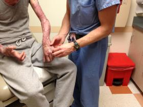 Brian Drolet, MD examines his patient's burn-scarred hand.