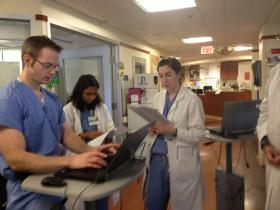 Anne Kuritzky presenting a patient to her attending on morning rounds in the SICU.