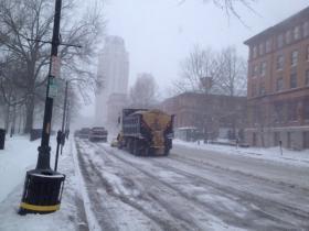 A team of snow plows scrape down Providence streets on Sunday.