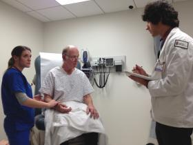 Kaminski and a nursing student assess the patient.
