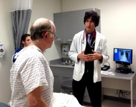 "2nd year Brown med student Peter Kaminski talks to a ""standardized patient"" during an interprofessional training exercise."