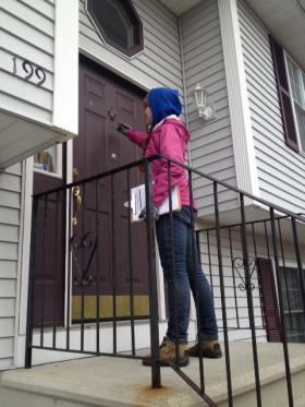 Same-sex marriage supporter Margaret Hughes knocks on a door in Woonsocket