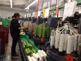 Spools of yarn whirl through the braiding machine
