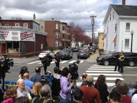 Media and residents look on as police surround house where suspects are believed to have lived.