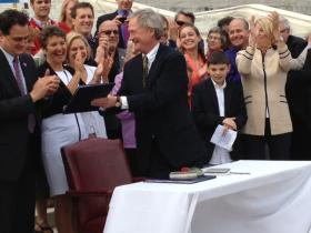 Governor Lincoln Chafee presents Rhode Island's new same-sex marriage law to openly gay lawmakers, House Speaker Gordon Fox and state Senator Donna Nesselbush