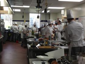 Culinary and medical students pause for direction from professor Todd Seyfarth (at right, without a toque)