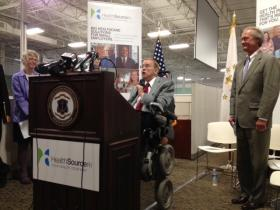 Gov. Lincoln Chafee looks on as Congressman Jim Langevin talks about the importance of health insurance at the HealthSource RI ribbon cutting.