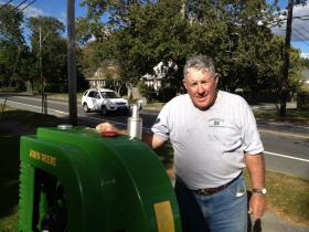 Lyle Booth stands near one of his John Deere tractors out front his home on Route 114 in Bristol.