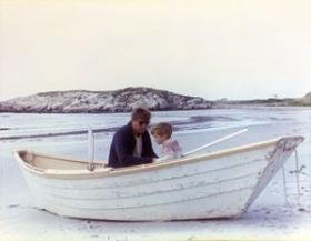 President John F. Kennedy sits with his son, John F. Kennedy, Jr., in a rowboat on Bailey's Beach in Newport, Rhode Island.