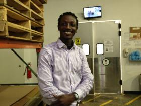 Andrew Kamara, Edesia's shipping manager, leads a tour of the factory floor.