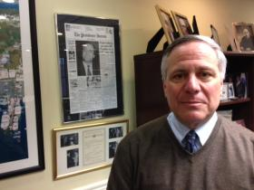 Paolino in his downtown offfice, near a copy of a front-page ProJo story heralding his 117-vote victory in the 1984 race for mayor.