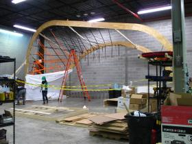 The two pieces of wood are two out of the five ribs that will make up the enclosure of the solar house. The mock up ribs are made out of wood in order to adhere to Rhode Island building codes. The team will use steel ribs when they build the final solar house in Versailles.