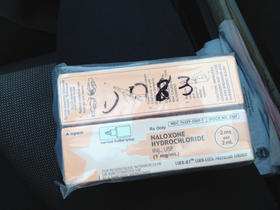 A kit containing two doses of naloxone, via nasal spray.