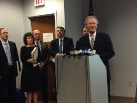 Chafee announcing the proposed pension settlement on February 14.