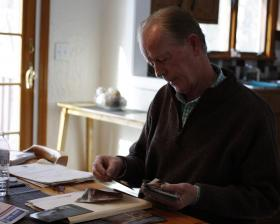 Paul Prendergast reviews photos of the flood damages to his home he has documented over the years.