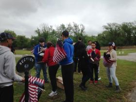 Students from Pawtucket's Alternative Learning Program gather flags to place on the graves of veterans.