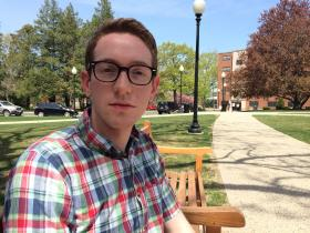 John Clarke sits on a bench at Providence College, where he will graduate with thousands of dollars in student debt.