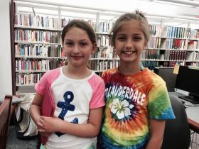 Isabella and Sophia Dauphine picking summer reads at the Cumberland Public Library.