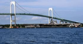 The ex-USS Saratoga glides under the Newport Pell Bridge as it starts its journey to Brownsville, Texas.
