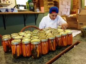 Monica Camacho sits behind dozens of labelled jars of pickled carrots ready to be sold at farmer's markets.