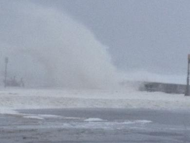 Waves crash over Narragansett sea wall.