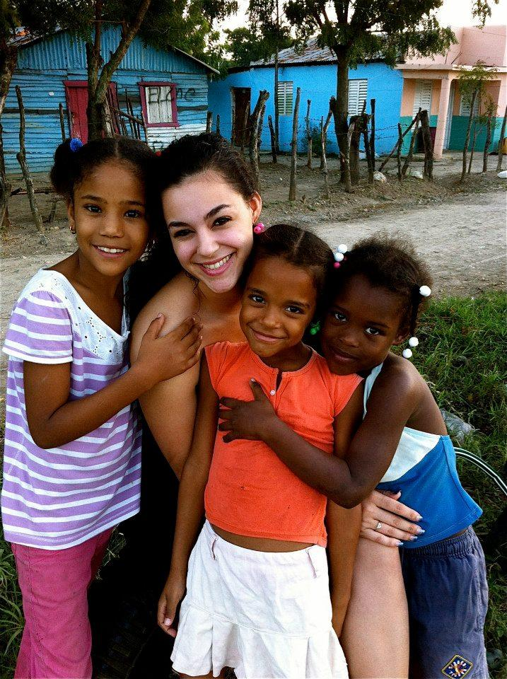 URI junior Britanny Alejo with young learners at literacy center Batey Libertad, Dominican Republic