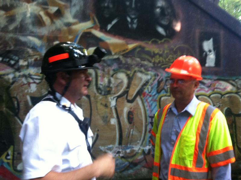Members of the inspection crew chat after taking the mile-long hike through the tunnel