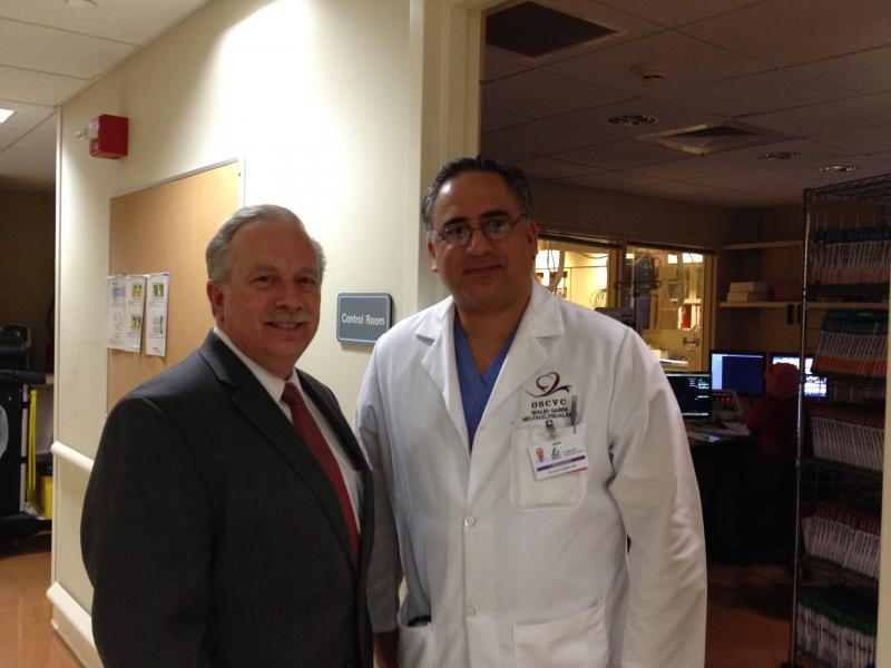"Landmark president Richard Charest, left, and Walid Saber, MD, cardiologist, talking in front of Saber's ""cath lab"" about celebrating when the deal finally goes through"