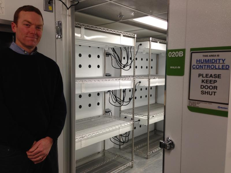 Biology professor Mark Johnson stands next to one of two large walk-in growth rooms, where thousands of smaller plants can be grown for research over the summer when it's too hot in the greenhouse.