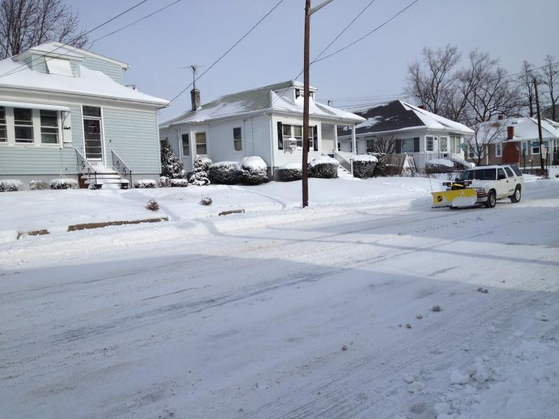 Crews scrape along the streets in Cranston as Rhode Island digs out Friday afternoon.