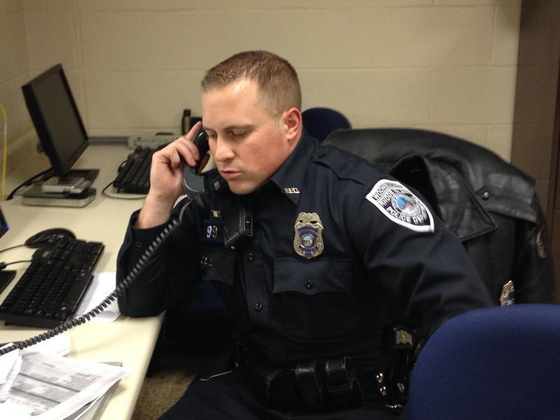 Woonsocket, RI police officer Matt Oliver on the phone at police headquarters, before his shift.