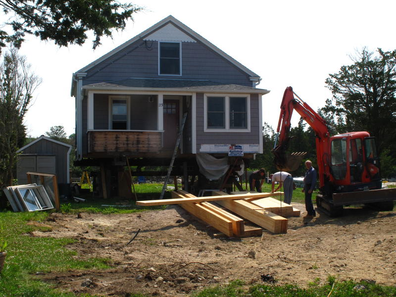 Tom Retano's three-bedroom house in Misquamicut is temporarily elevated off its original foundation, as work to permanently elevate the house 15 feet above sea level began this summer.