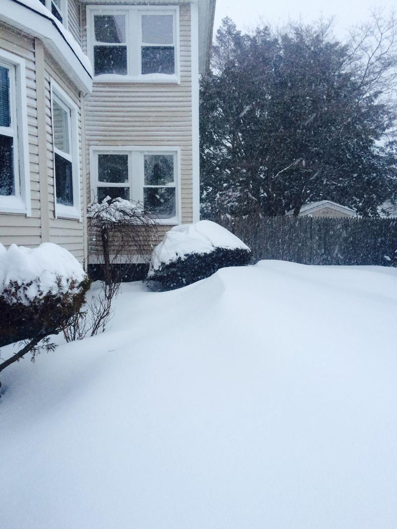 Snow drifts pile up Tuesday morning near a home in the Elmhurst neighborhood of Providence