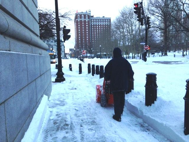 A snow blower clears off a side walk in downtown Providence Wednesday morning