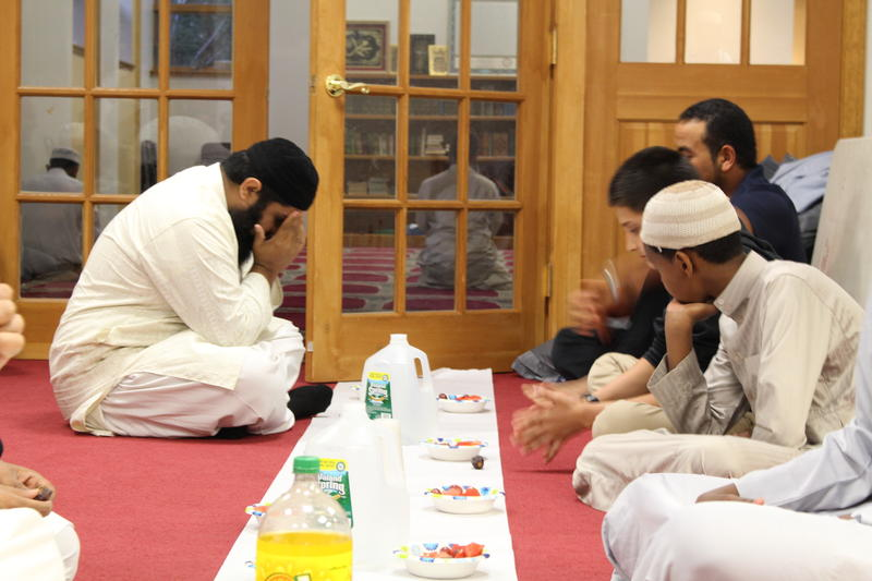 Imam Mufti Ikram (left) prays before he breaks his fast.