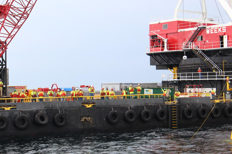 Many workers on the barge greeted nearly 150 passengers on a ferry, getting a closeup of the wind farm's early construction stage.