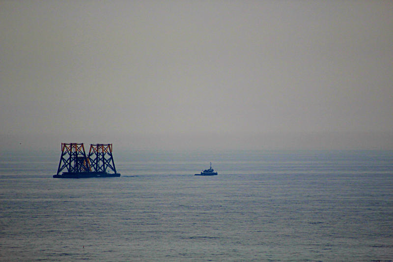 A tugboat pulls two foundations toward the site of Deepwater Wind's offshore wind farm three miles off the coast of Block Island.