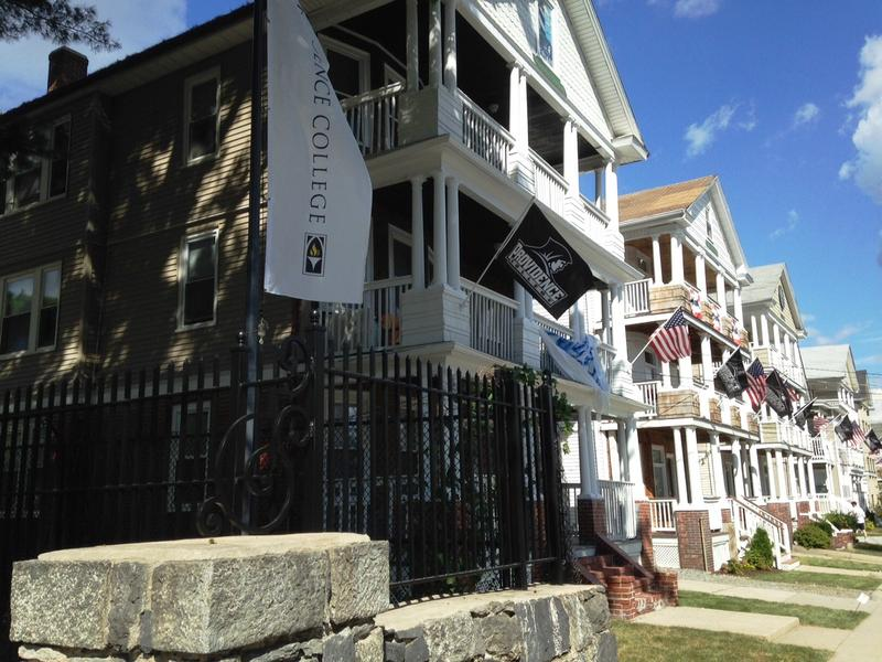 A row of triple decker apartments marketed to students, abut the Providence College campus
