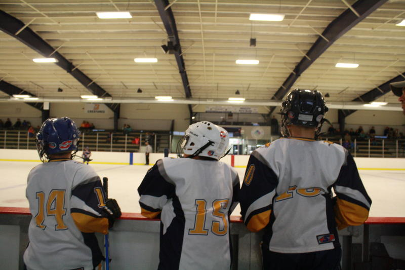 Kids watch as their teammates compete in a Sunday morning game at Levy Rink in Burrillville.
